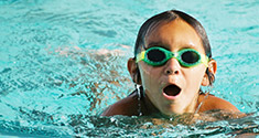 Child with goggles swimming in pool