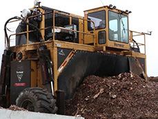 A large machine is used to turn the compost