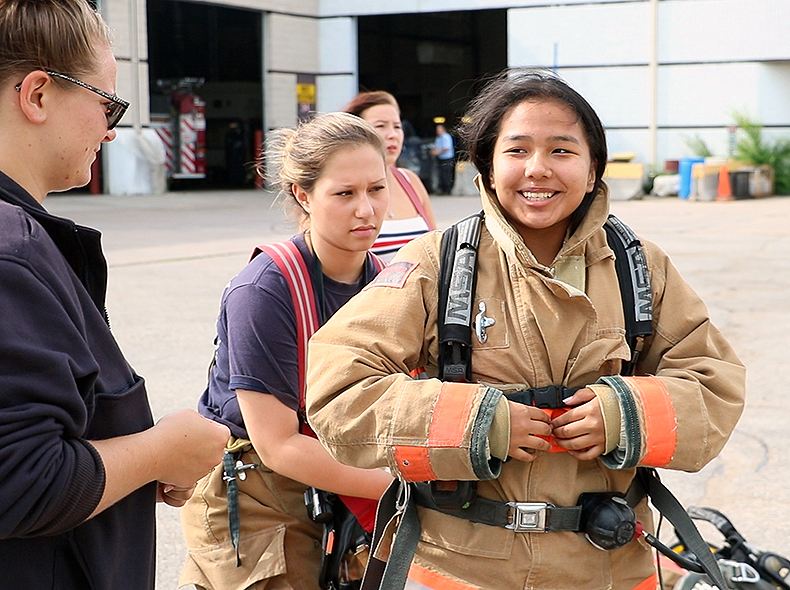 A youth participant being helped into firefighter gear