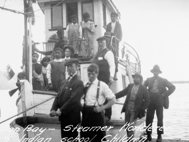 This image shows children on boats going to the Cecilia Jeffrey Indian Residential School near Shoal Lake.