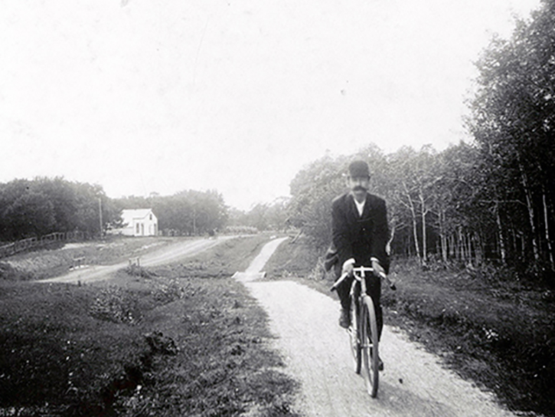 Credit: Archives of Manitoba, Item: N4549. Cyclist on Portage Avenue at Silver Heights with Sturgeon Creek in the background, circa 1900.