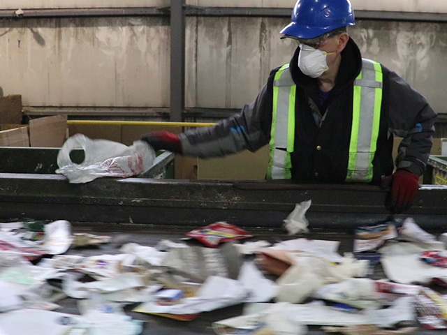 Employees have to remove plastic bags by hand at the recycling sorting facility.