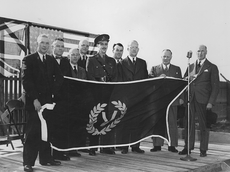 Group of unidentified men and a member of the military holding up a Victory Day flag