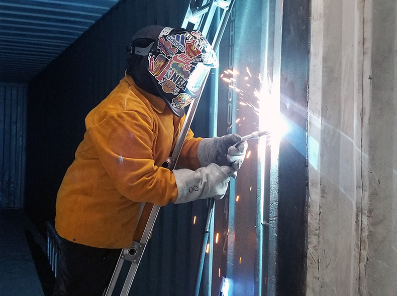student standing on a ladder welding