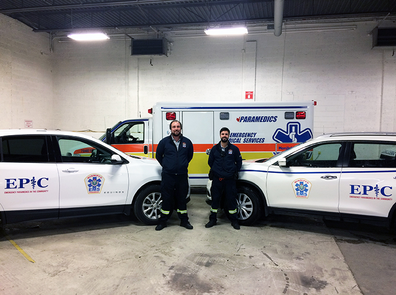 Two paramedics standing next to an ambulance