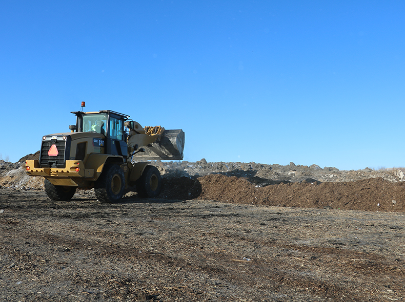 Front-end loader pushing biosolids at landfill