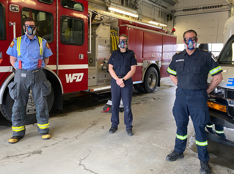 Fire and Paramedic staff wearing masks inside firehall