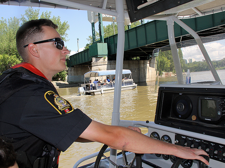 Police officer driving boat on a river