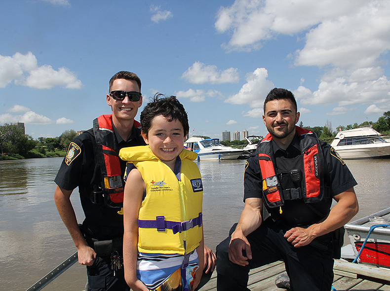 Boy wearing lifejacket standing next to police officers