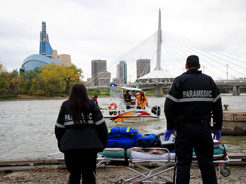 paramedics waiting along river for a boat