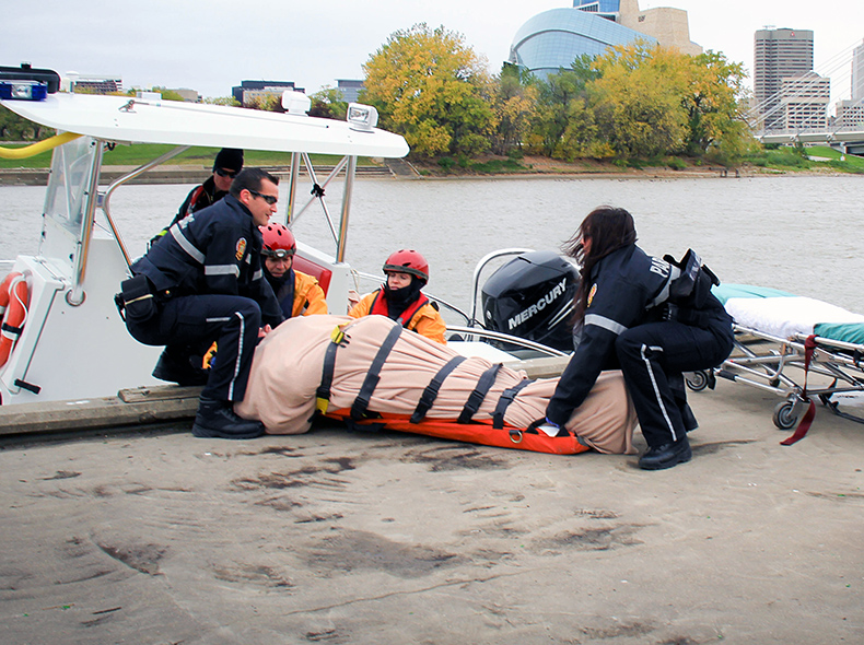 paramedics lifting a back board off of a boat