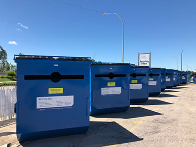 Image of a row of containers at a recycling depot